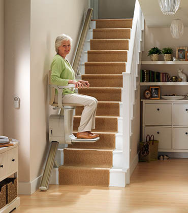Straight Stair lift in home being used by elderly woman